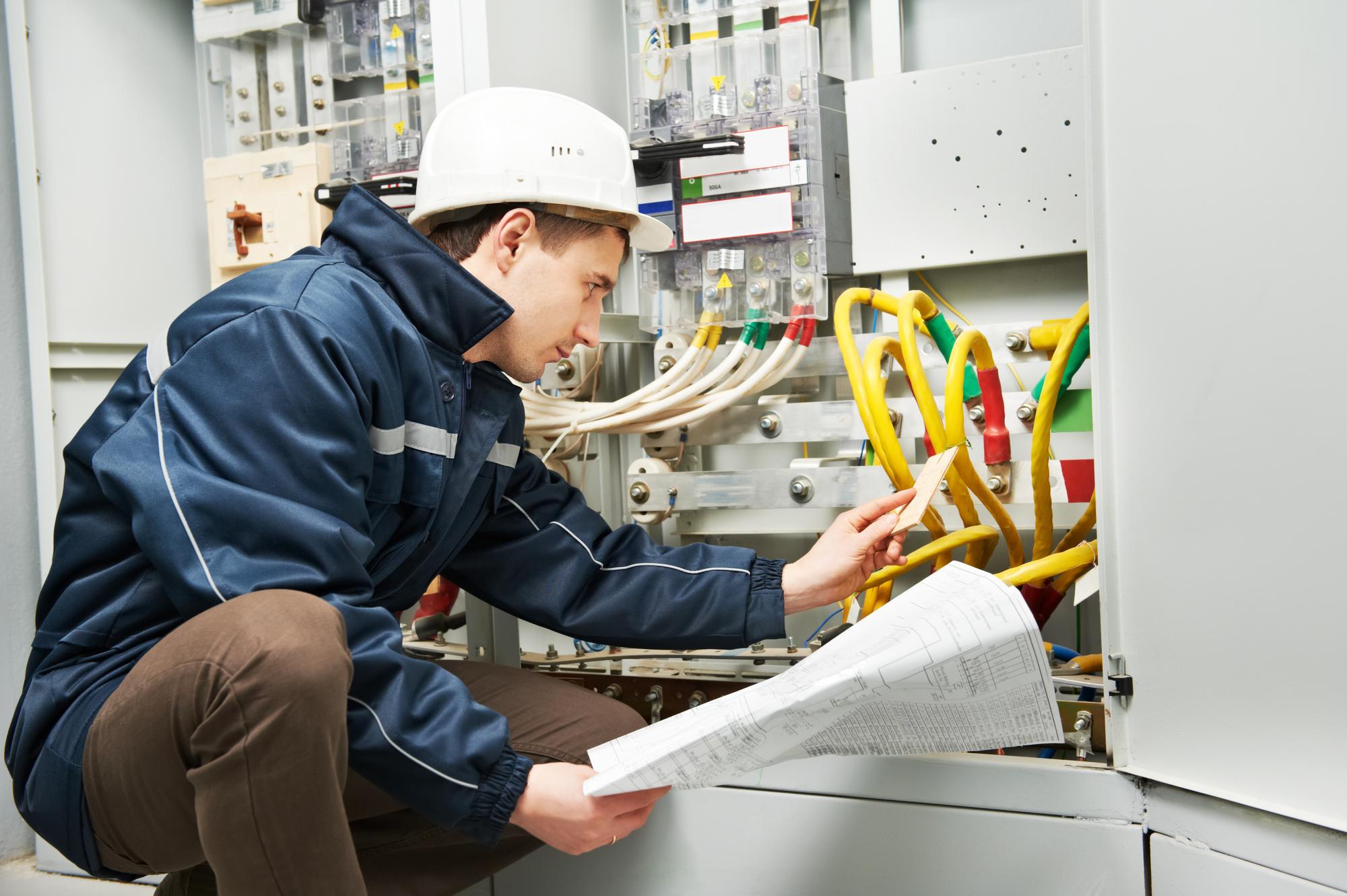 Imagen en la que aparece un trabajador revisando una instalación de cables